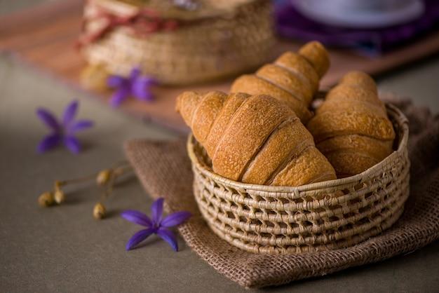 Petit pain croissant dans le panier sur la table du petit déjeuner