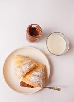 Petit pain de croissants frais avec du chocolat sur la plaque, verre de lait sur le blanc