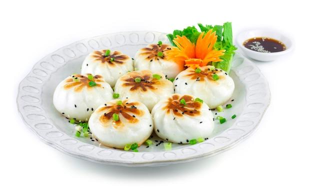 Petit pain cuit à la vapeur à la poêle ou sheng jian bao rempli de porc haché et de légumes croustillants moelleux
