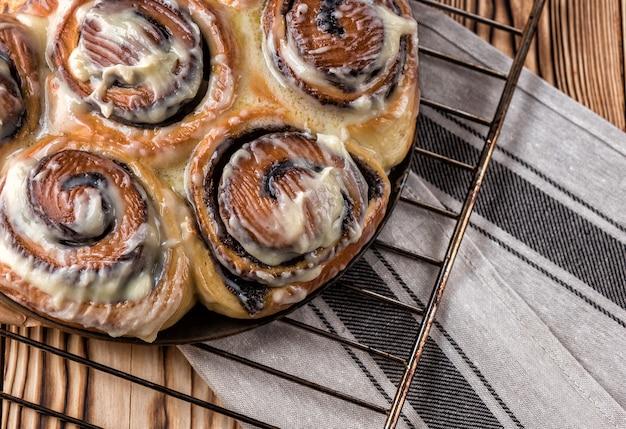 Petit pain avec du thé sur une table en bois sur une grille métallique sur un fond en bois