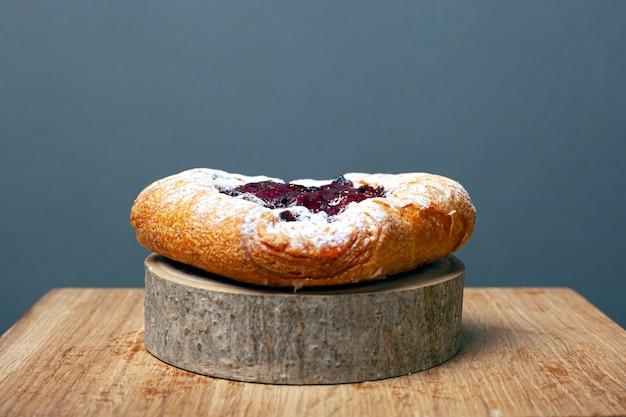 Petit pain feuilleté aux cerises et crème pâtissière saupoudré de sucre en poudre sur un support de forêt en bois sur un fond gris.