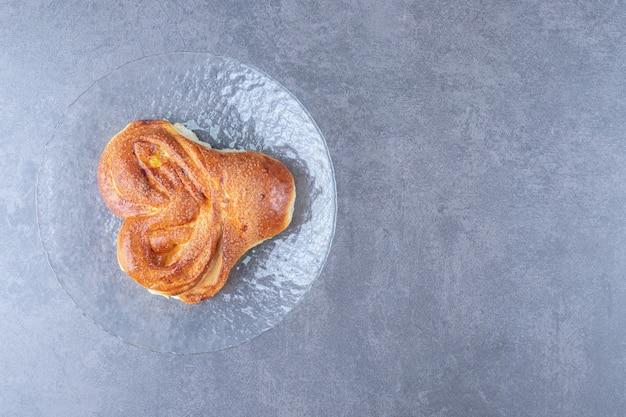 Petit pain en forme de coeur sur la plaque de verre sur table en marbre.