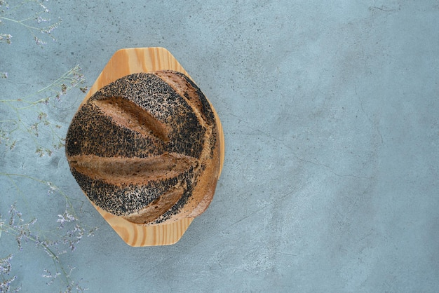 Petit pain frais sur plaque de bois.