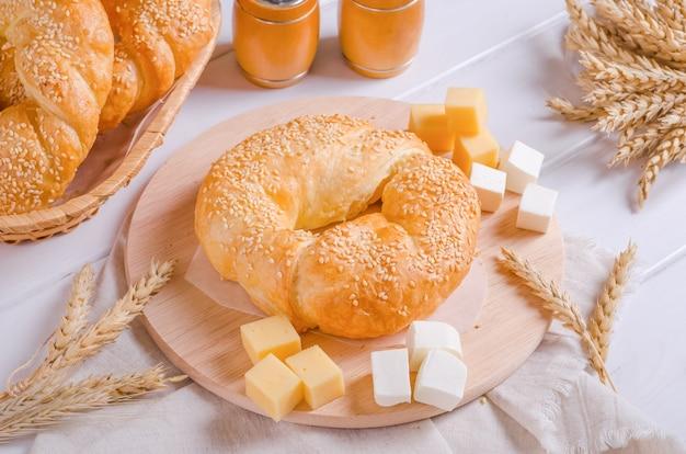 Petit pain frais et savoureux avec garniture au fromage sur une planche de bois ronde sur fond de bois blanc