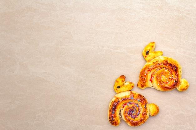 Petit pain frais sous la forme d'un lapin de pâques. le concept de boulangerie de vacances pour enfants. sur la surface en pierre, copie espace, vue de dessus.