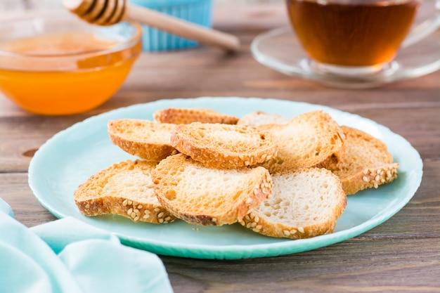 Petit pain grillé baguette sur une assiette sur une table en bois thé et miel pour le petit déjeuner