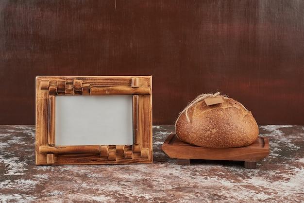 Petit pain sur marbre sur planche de bois.
