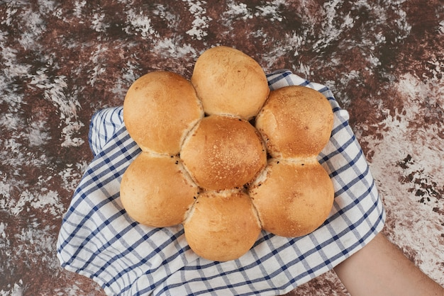 Petit pain sur marbre sur serviette à carreaux.