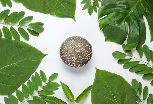 Petit pain noir aux graines de sésame sur fond blanc avec des feuilles tropicales vertes