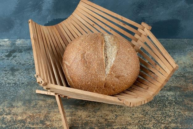 Un petit pain de pain brun frais sur panier en bois