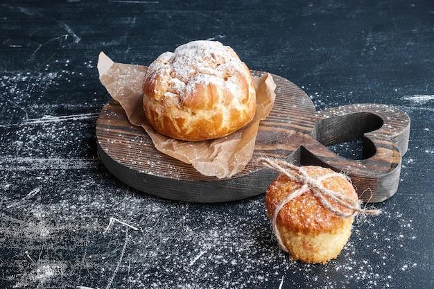 Petit pain de pâte feuilletée avec petit gâteau sur une planche de bois.