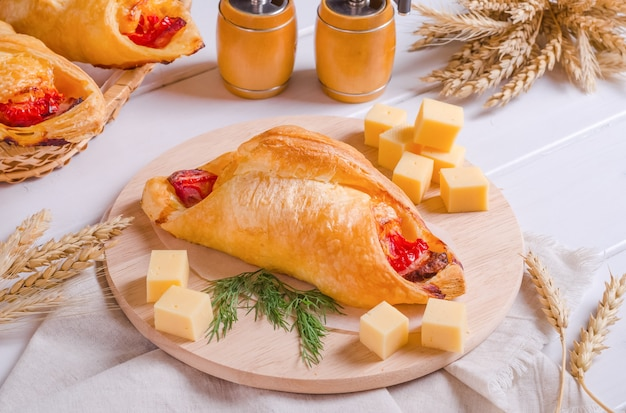 Petit pain de pâte feuilletée savoureux frais avec garniture au fromage sur une planche de bois ronde sur fond de bois blanc