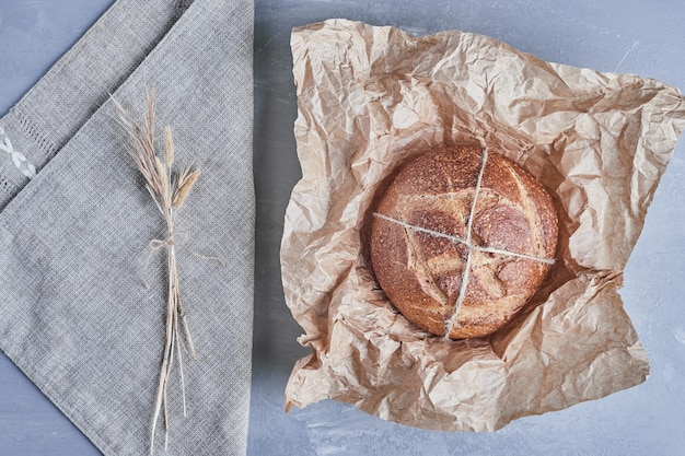 Petit pain rond fait à la main sur un morceau de papier.