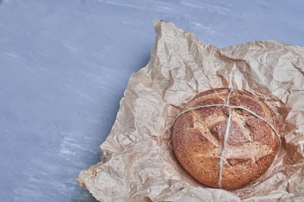 Petit pain rond fait à la main sur un papier rustique.
