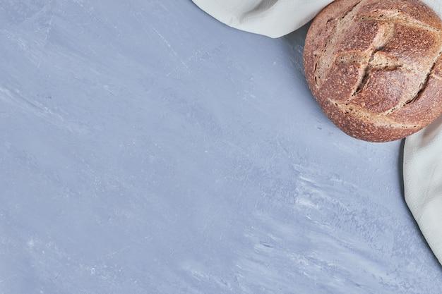 Petit pain rond fait à la main sur table bleue.