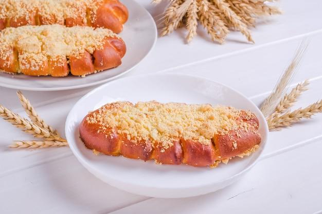 Petit pain savoureux frais avec arrose sur plaque blanche sur fond de bois blanc