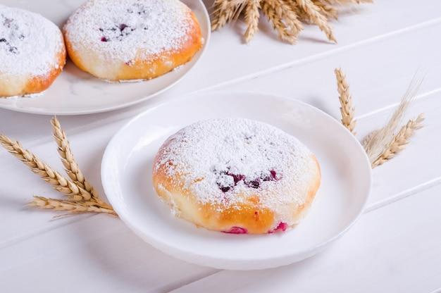 Petit pain savoureux frais avec du sucre en poudre sur une plaque blanche sur fond de bois blanc