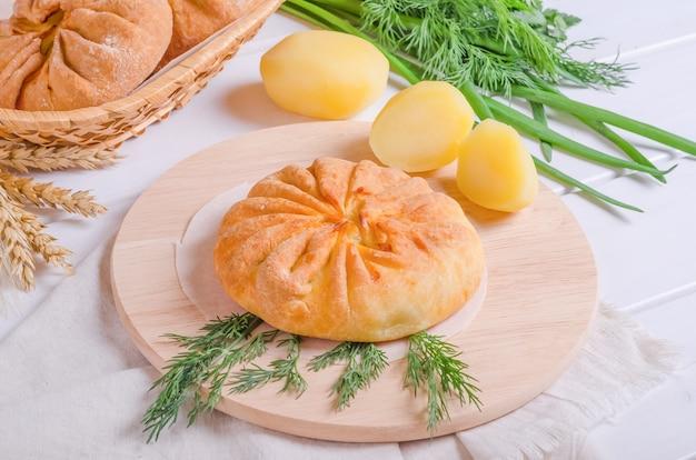 Petit pain savoureux frais avec garniture de pommes de terre sur une planche de bois ronde sur fond de bois blanc