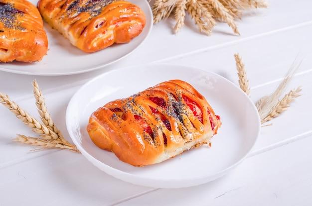 Petit pain savoureux frais avec remplissage de baies sur plaque blanche sur fond de bois blanc