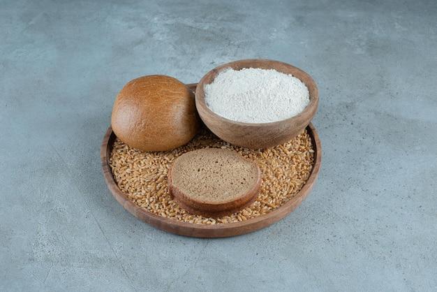 Petit pain de seigle avec bol de farine sur plaque de bois.