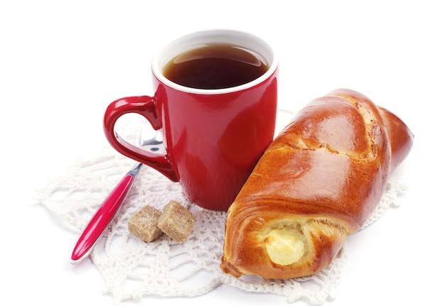 Petit pain sucré avec du fromage cottage et une tasse de thé sur fond blanc
