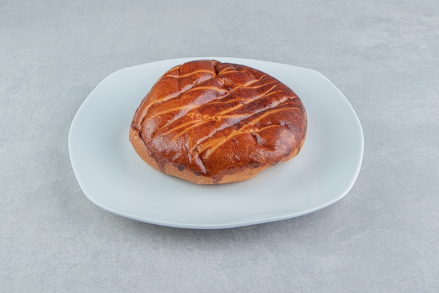 Petit pain sucré fait maison sur plaque blanche.