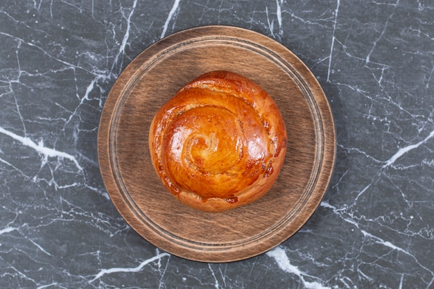 Petit pain sucré sur la planche, sur la surface en marbre
