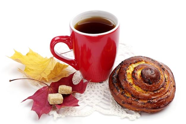 Petit pain sucré rond et tasse de thé sur fond blanc