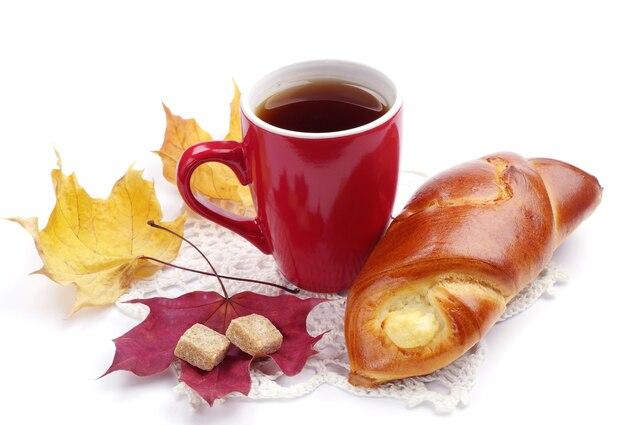 Petit pain et tasse de thé sur fond blanc