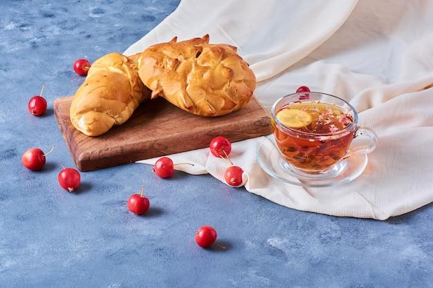 Petit pain avec une tasse de thé sur une planche de bois sur bleu