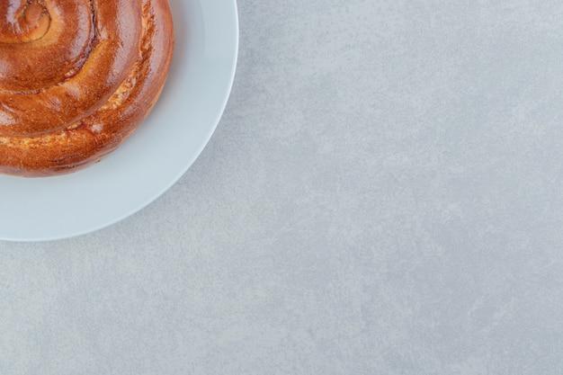 Petit pain tourbillon doux sur plaque blanche.