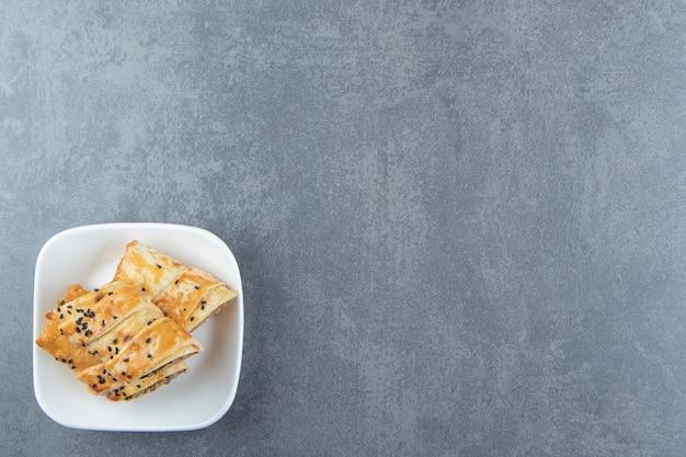 Petit pain tranché farci de viande sur plaque blanche.
