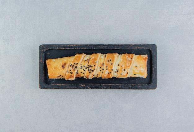 Petit pain tressé farci de viande sur plaque noire.