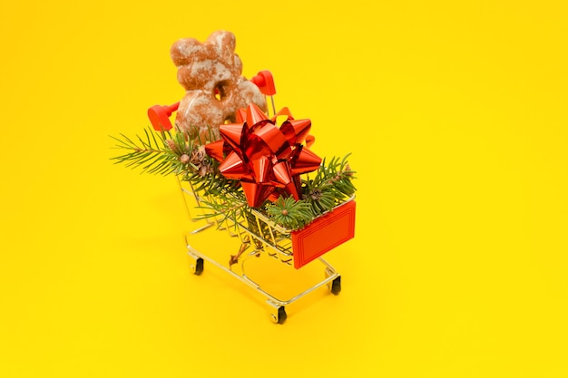 Petit panier avec des branches de sapin, noeud cadeau et ours au gingembre sur fond jaune.