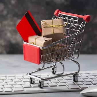 Petit panier avec des cadeaux et une carte de crédit sur un clavier d'ordinateur portable