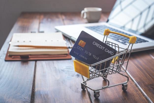Un petit panier avec une carte de crédit à l'intérieur et à l'arrière est un bureau. concept utiliser le crédit pour faire du shopping.