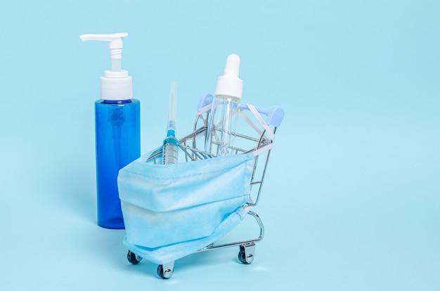 Petit panier décoratif avec un masque médical de protection, une seringue, un antiseptique et du savon dans des banques sur fond bleu.