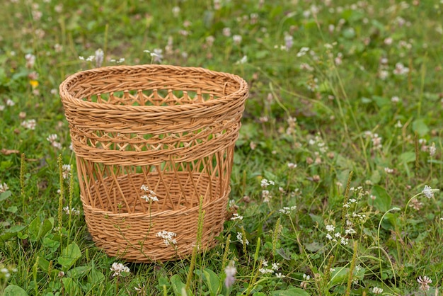 Un petit panier en osier vide se dresse dans un pré vert