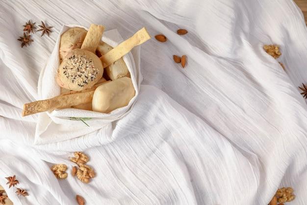 Petit panier en serviette en tissu blanc avec du pain blanc à l'intérieur.