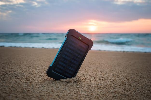 Petit panneau solaire portable près de l'océan atlantique. powerbank pour charger les téléphones portables et autres appareils via usb. batterie solaire sous le soleil sur fond de belle aube et ciel nuageux.