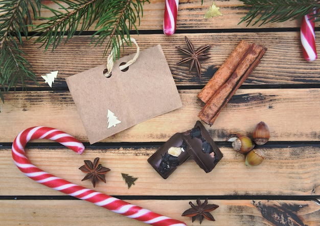 Petit papier brun mis sur un fond en bois rustique avec des cannes de bonbon aux épices et au chocolat