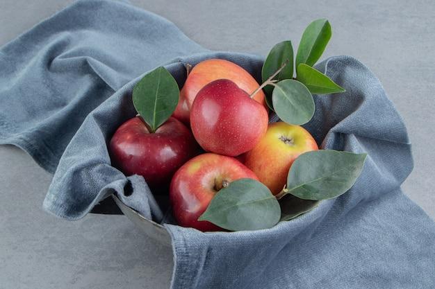 Petit paquet de pommes enveloppé dans un morceau de tissu sur du marbre.