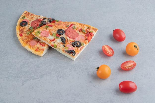 Petit paquet de tomates et tranches de pizza sur marbre