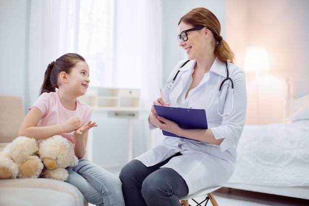Petit patient. adorable belle femme médecin parlant avec une fille pour écrire les symptômes tout en portant le tableau des patients