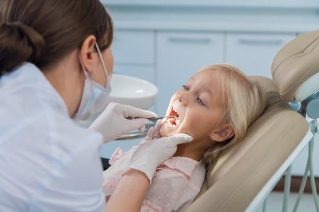Un petit patient ouvre la bouche pour un examen dentaire