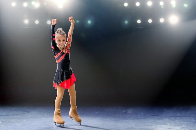 Le petit patineur monte sur des anneaux dans la robe rouge et noire sur la patinoire