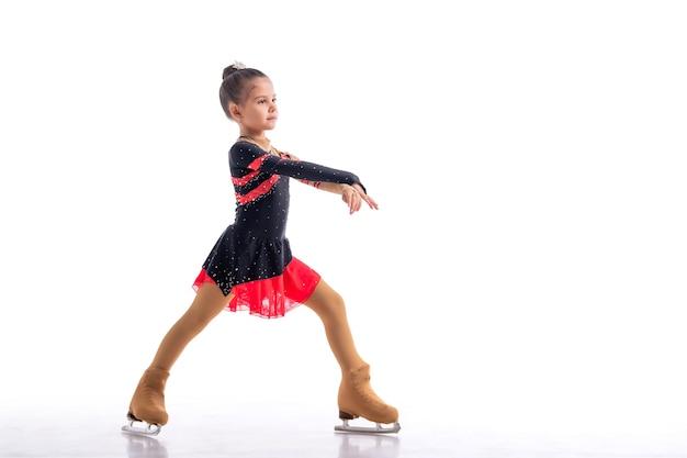 Petit patineur posant en robe rouge et noire sur glace isolé sur fond blanc
