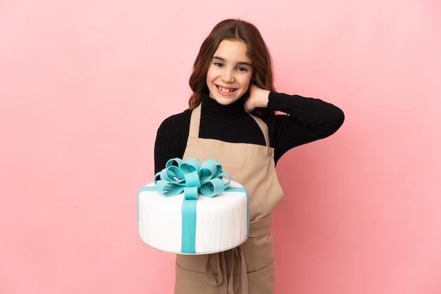 Petit pâtissier tenant un gros gâteau isolé sur fond rose en riant
