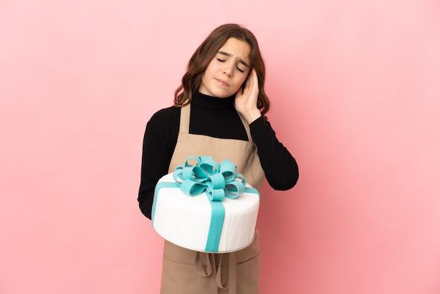 Petit pâtissier tenant un gros gâteau isolé sur un mur rose avec des maux de tête