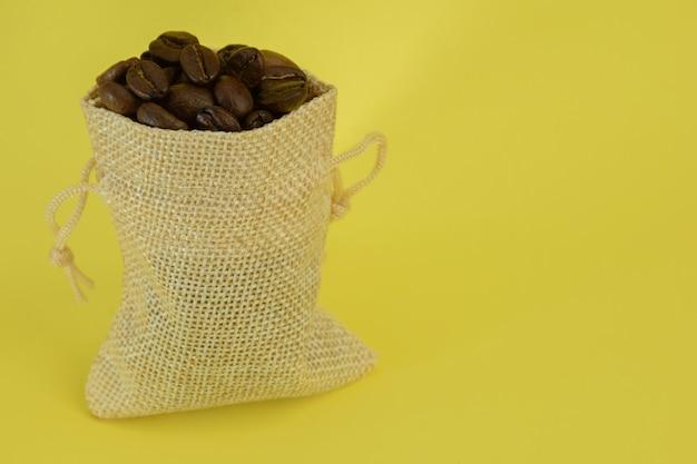 Un petit petit sac avec des grains de café se tient droit sur un fond jaune